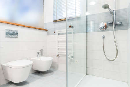 shower stall: Modern bathroom with white tiles and transparent shower stall