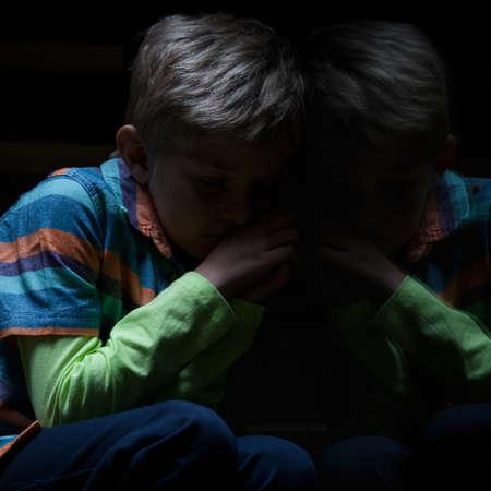 Mening van bange jongen zittend op de trap