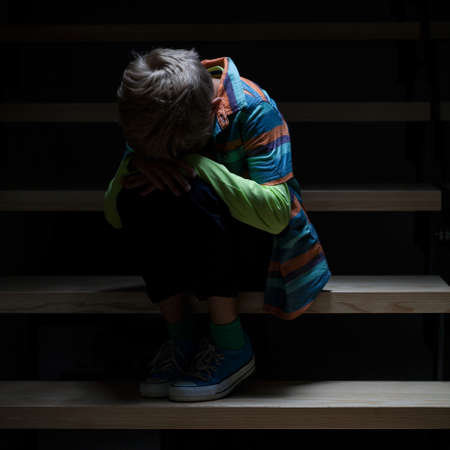 View of crying boy sitting on staircase Banco de Imagens