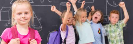 niños felices: Feliz niña de la escuela, en el grupo de fondo de los niños levantando las manos en alto, panorama Foto de archivo