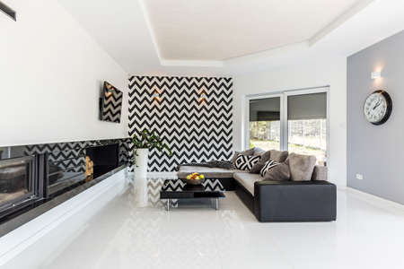 living room design: Bright living room with stylish couch and mosaic theme on the wall