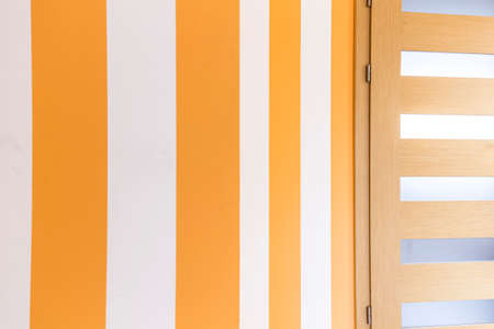 Striped yellow wall in the room with horizontally striped door