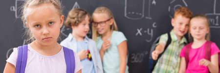 violencia: niña de la escuela triste, en los niños que ríen y fondo detractora ella, panorama Foto de archivo