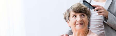 home care: Female carer brushing older womans hair