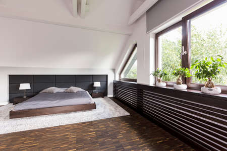 double bed: Elegant bedroom with low double bed and decorative bonsai trees