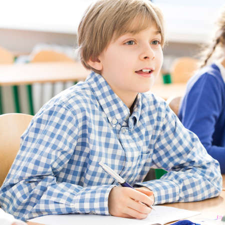Little excited boy writing an essay during lesson sitting in school bench Stock Photo