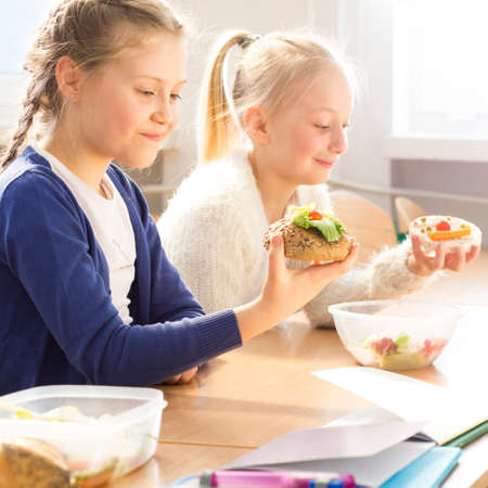 Two young pretty girls eating together healthy sandwiches during lunch break at school Stock Photo