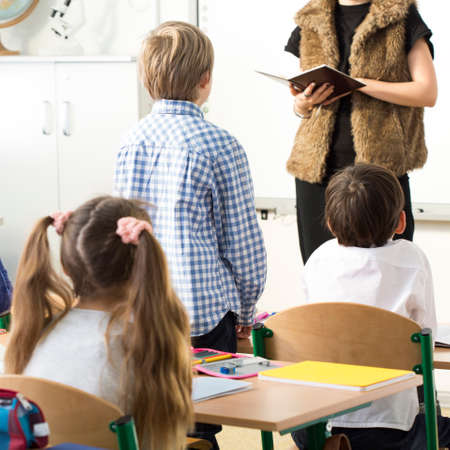 presence: Elegant teacher checking the pupils presence during lesson in primary school Stock Photo