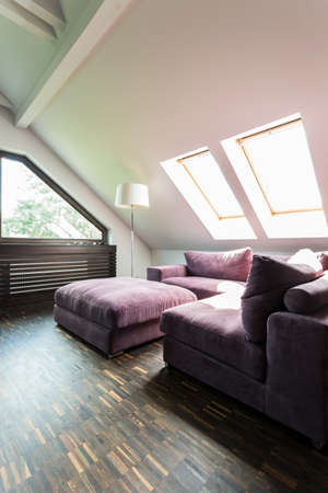 pouffe: Purple corner sofa and pouffe in an illuminated attic lounge room