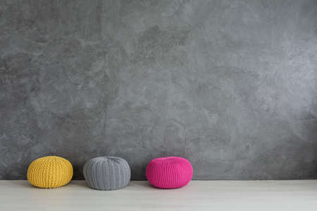 hassock: Three colorful wool poufs in concrete wall interior