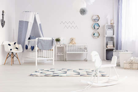 lightsome: Bright and cozy room for a small child with rocking horse, bed and cradle Stock Photo