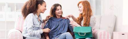 shopaholics: Woman holding new blouse in front of her and chatting with friends Stock Photo