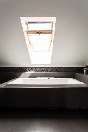 attic window: Rectangular bath in dark enclosure under an open attic window Stock Photo