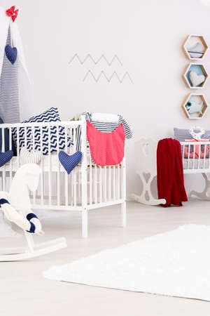 lightsome: Crib with a red blanket and a rocking horse in a bright room Stock Photo