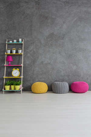hassock: Colorful decorations and poufs in concrete wall interior Stock Photo