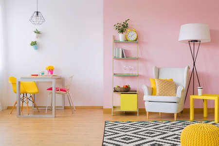 Pink living room with white and yellow furniture Standard-Bild