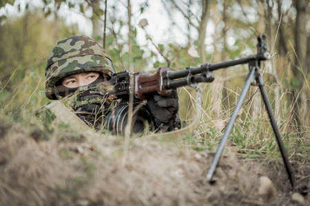 armed: Masked soldier aiming from machine gun on army range Stock Photo