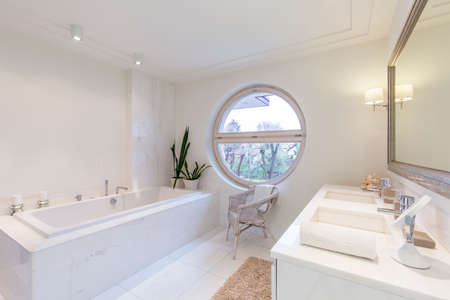 lightsome: Bright minimalist bathroom with round window, bath, two sinks and large framed mirror