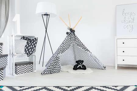 Zwart en wit kind kamer met tapijt, tent en dressoir Stockfoto