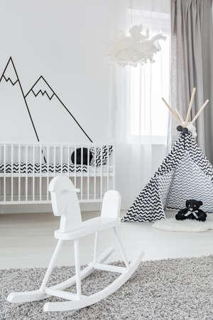 흰색 락 말과 플레이 텐트로 여자애 방