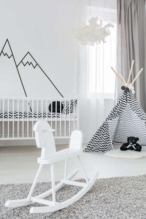 Baby girl room with white rocking horse and play tent