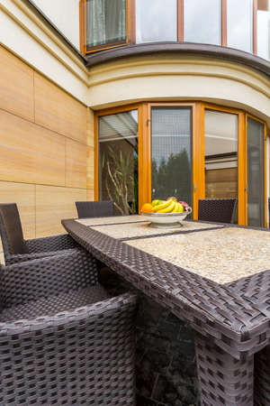 conservatory: Close-up of a dark rattan table with chairs in the backyard of a villa