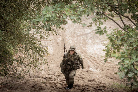 proving: Male soldier with weapon in uniform during military maneuver on army training ground