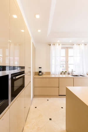 lightsome: Fully equipped kitchen with bright furniture and modern oven Stock Photo