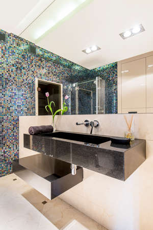 gleaming: Modern bathroom with gleaming mosaic tiles and a large mirror