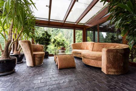 Komfortable Plüsch in einem Wintergarten gesetzt Wohnzimmer mit dunklen Steinboden Standard-Bild