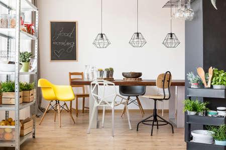 Kamer met gemeenschappelijke tafel, stoelen, industriële regale en kar