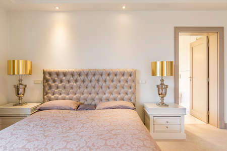 lightsome: Elegant master bedroom with double bed with quilted headboard Stock Photo