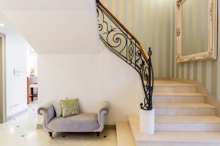 elegant staircase: Elegant staircase with decorative railing, big framed mirror and patterned couch Stock Photo