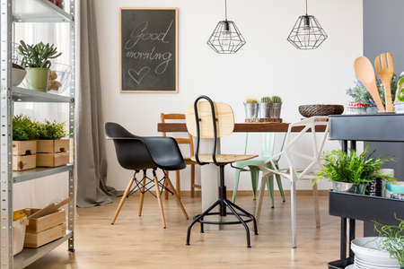 Dining room with modern chairs, table and simple regale