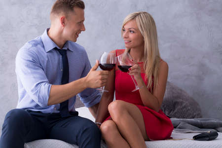 Young elegant couple drinking wine on a bed