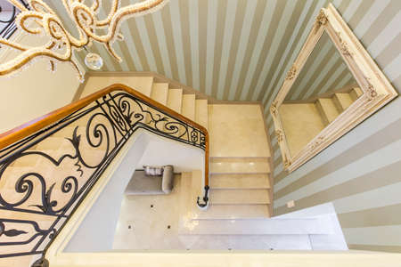 striped wallpaper: View from the top of the stairs with a decorative railing and large mirror on the wall Stock Photo