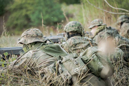 maneuver: Camouflaged army soldiers with machine guns lying on firing range