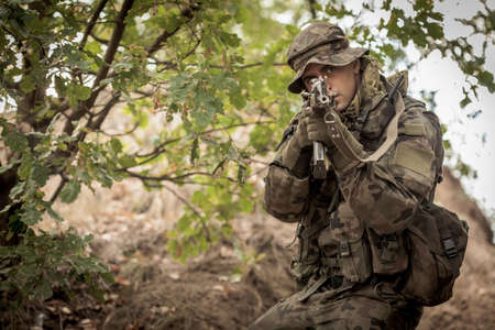maneuver: Male armed sniper aiming from weapon during tactical maneuver