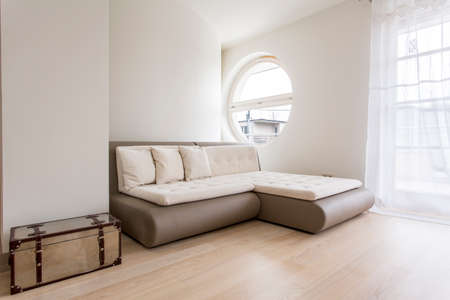 guest room: Bright guest room with a sofa bed and big round window Stock Photo
