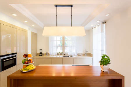 lightsome: Kitchen with a spacious wooden kitchen counter on which stand fruits and herbs