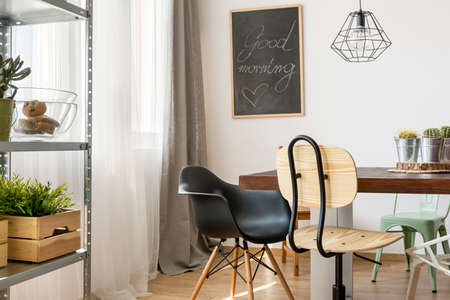 communal: Light room with communal table, chairs, industrial lamp and regale