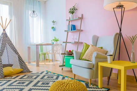 Modern colorful living room with armchair and tent Stock Photo