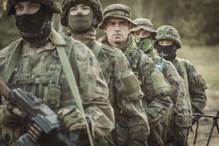 proving: Armed young masked soldiers participating in military training maneuvers