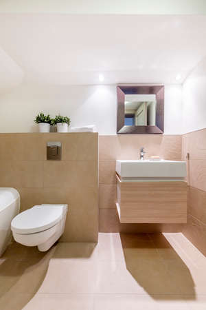 toilet sink: Chic travertine bathroom with toilet, sink and small mirror in earthy tones
