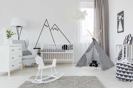 Kinderkamer met witte meubels, tapijt, tent en muursticker