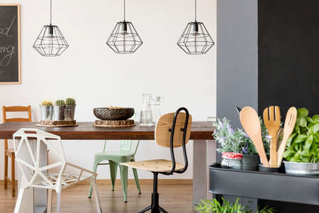 Room with communal table, chairs, pendant lamps, kitchen cart