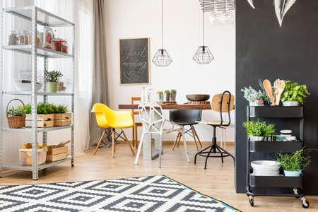 Open eetkamer met tafel, stoel en industriële hangerlamp Stockfoto