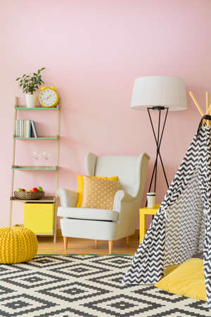Pastel iving room with armchair, lamp, shelf and tent