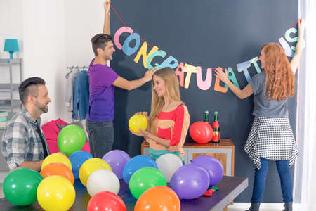 Friends preparing congratulations party, decorating room with balloons