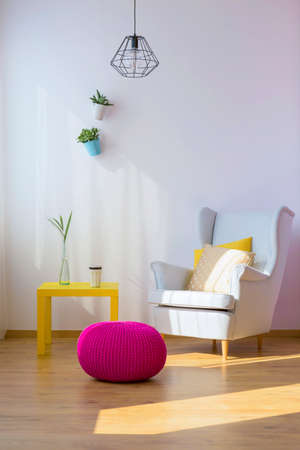 Armchair, pouf and table in a living room Stock Photo